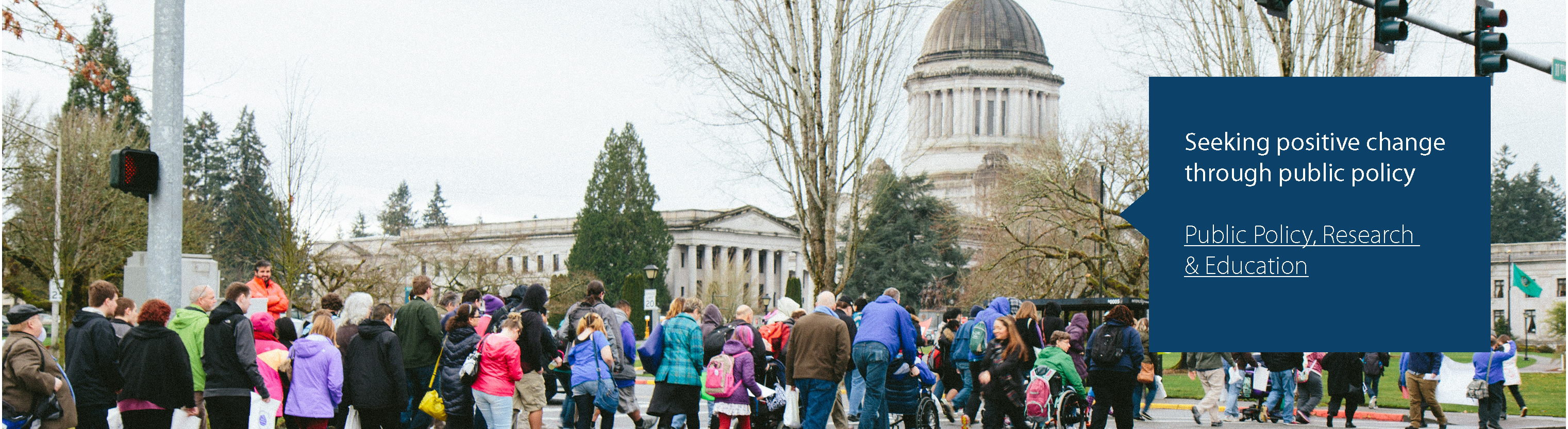 Seeking positive change through public policy. Public Policy Research, Analysis & Education Program. A group of people cross the street in Olympia, WA in front of the Capitol building.