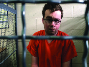 Josh Stuller sitting in a jail cell with glasses on and one eyebrow raised
