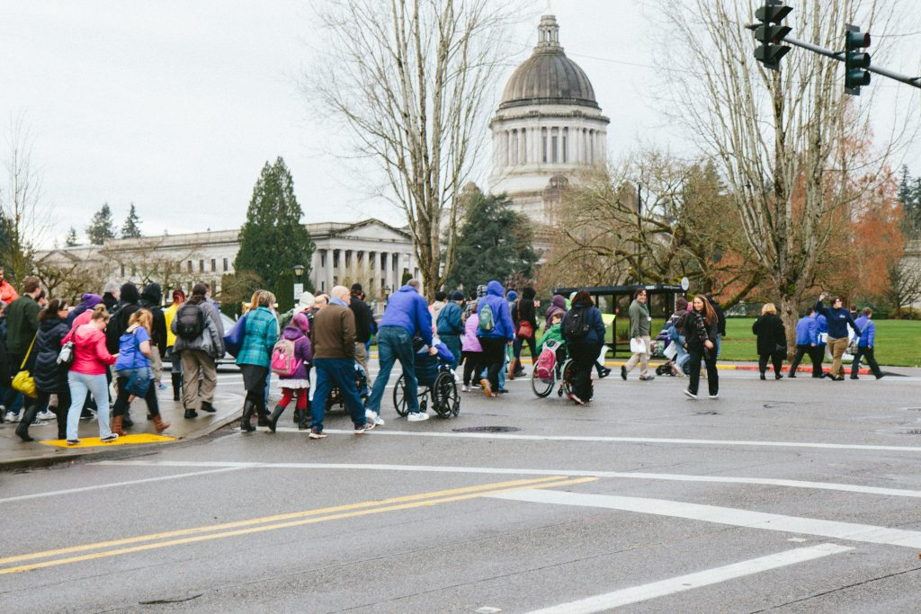 People cross the street in Olympia, walking and rolling towards the Capitol building.