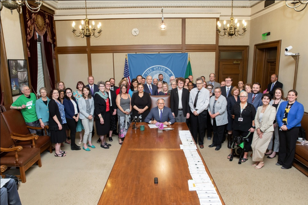 Photo of Trueblood advocates, DRW staff, and co-counsel standing around Governor Inslee while he signs the Trueblood bill, SB 5444.