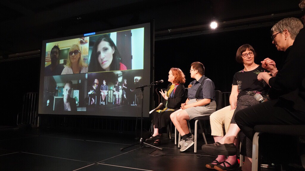 Parenting without Pity event panelists shown on the screen were able to participate in the discussion remotely via video chat. The moderator and in-person participants sat to the right of the screen.
