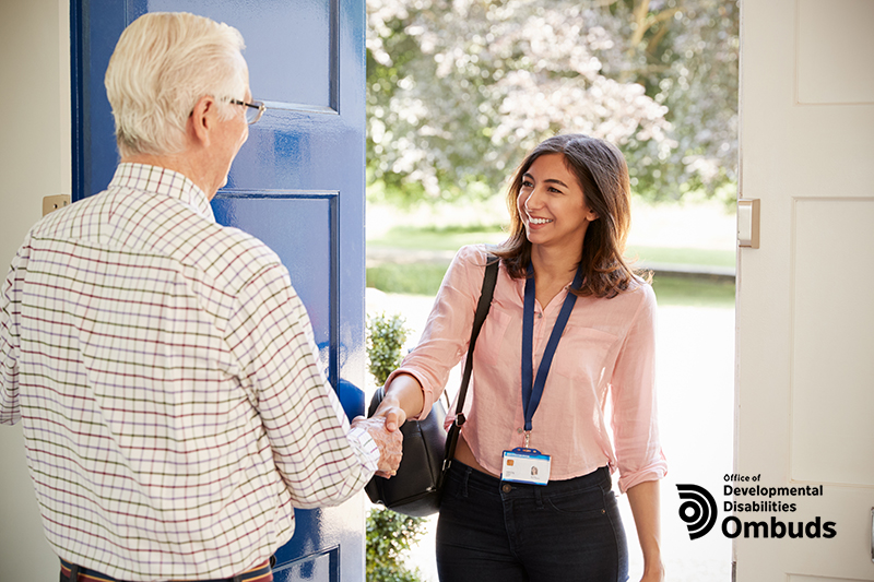 Smiling woman introduces herself in a doorway.