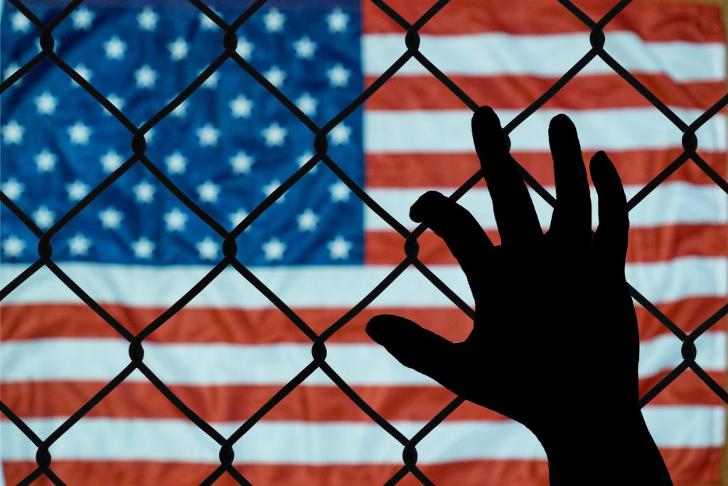 hand on fence behind american flag