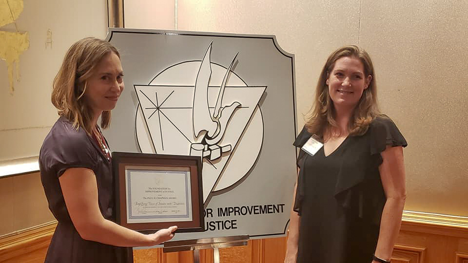 Two women standing with award