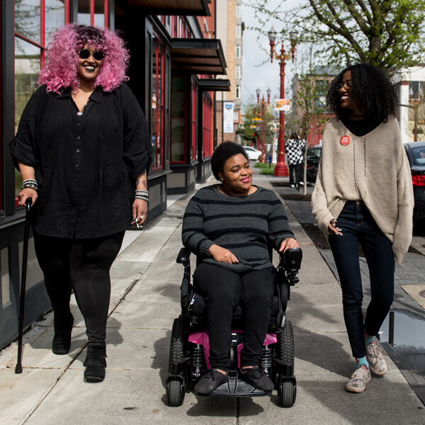 Three people on sidewalk. Person on the left is using a cane. Person in middle is in a wheelchair.