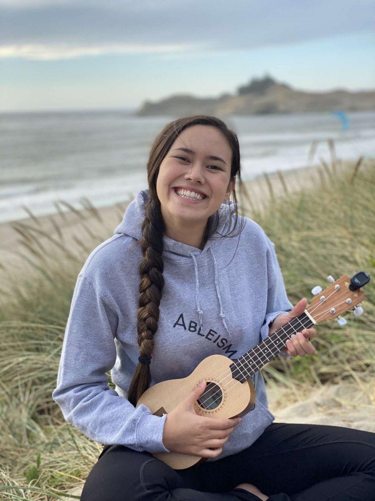 Christine sitting on a beach holding a ukulele and smiling.