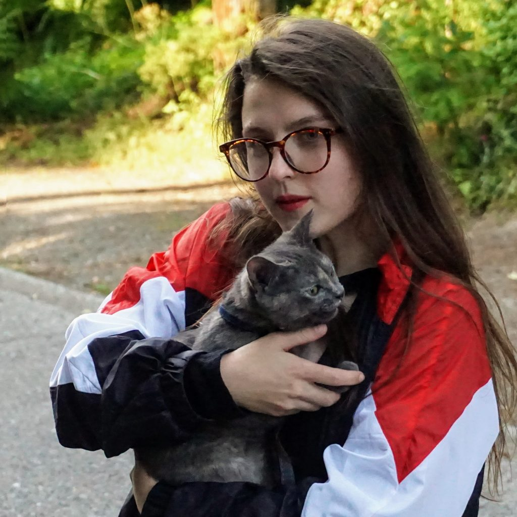 Picture of Rochelle wearing a red and white jacket and glasses, while holding a dark grey cat.