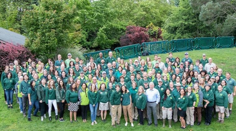Zoo staff wearing green shirts and standing together on a green lawn with trees in background.