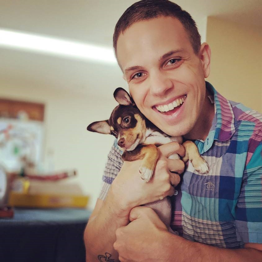 Person smiling at camera while holding a small brown and tan dog.