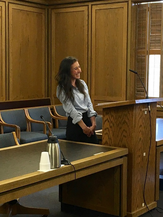 Reisha smiling and standing behind a podium in an empty courtroom.
