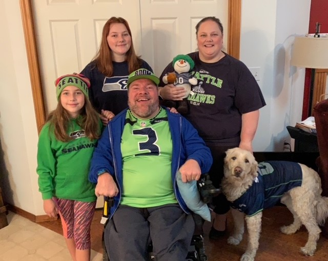 Photo of Shawn surrounded by his family and dog. They are all wearing Seattle Seahawks clothing.