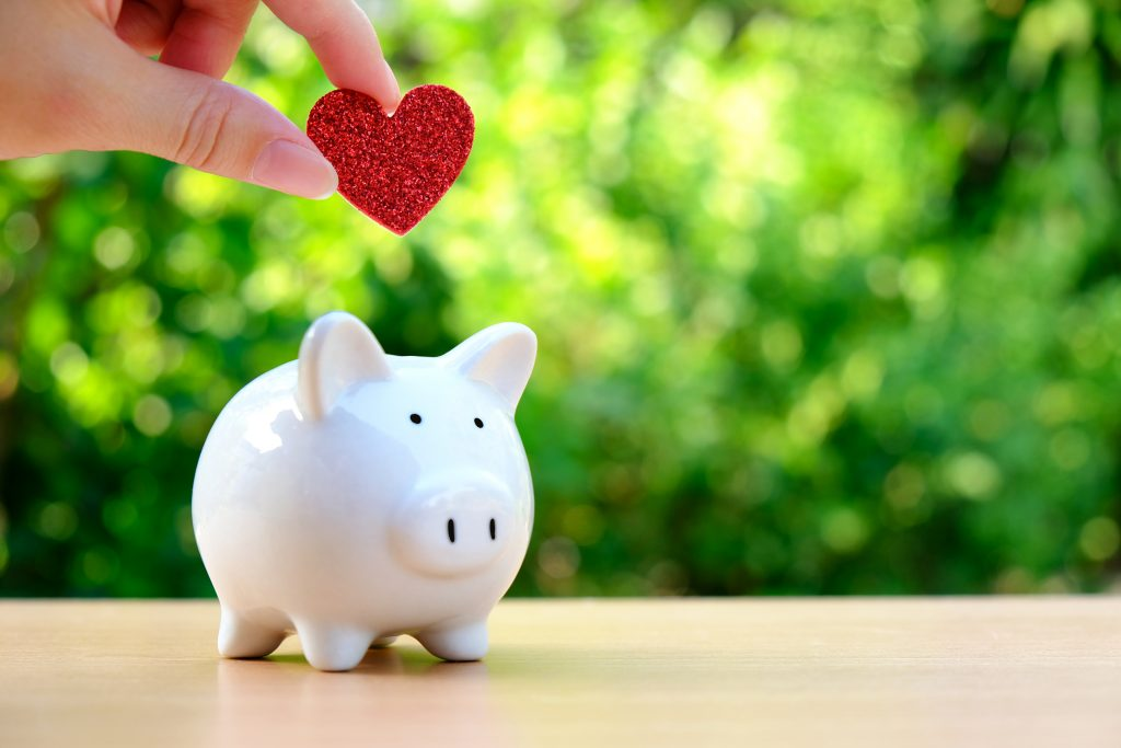 A white piggy bank on a beige table top in front of green bushes. A hand holding a small red heart shaped item is placing the item inside of the piggy bank.