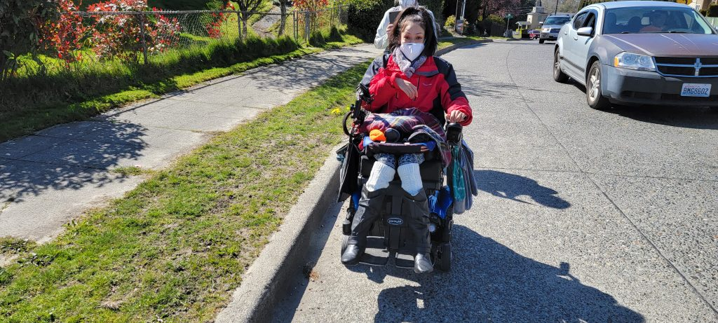 A brown skin woman in a power wheelchair rolls up the side of the street. There's a sidewalk next to her, and cars passing closely. She is wearing a mask and a red jacket, and her eyes look alarmed.