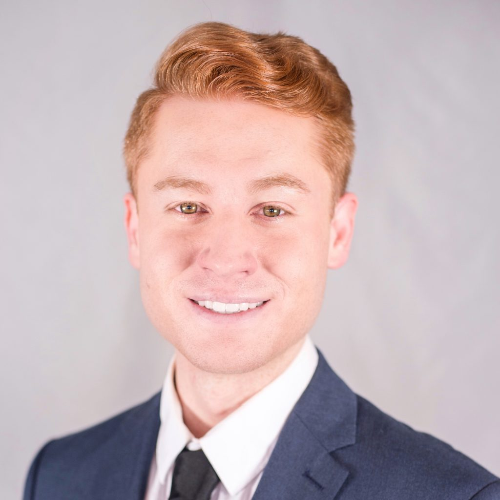 Headshot photo of Joshua wearing a navy blue tie and blazer with a white collared shirt beneath, while smiling at camera. He has short red hair.